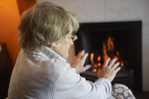 Older person sitting by a fire