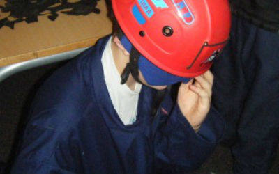 A young person in a caving helmet