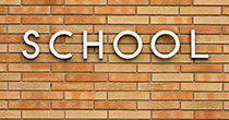 A school sign on a brick wall