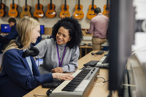 teacher giving help to pupil in music lesson