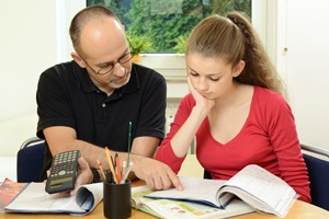 Picture of a man holding a calculator and pointing at a workbook in front of a school girl