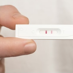 Hand holding a positive pregnancy test
