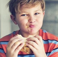 Caucasion boy in red and blue striped t-shirt eating a sandwich which he looks like he is enjoying