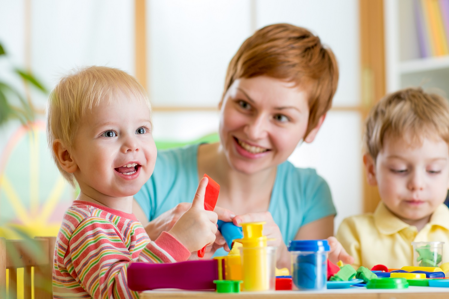 Woman with 2 young children playing with early years material