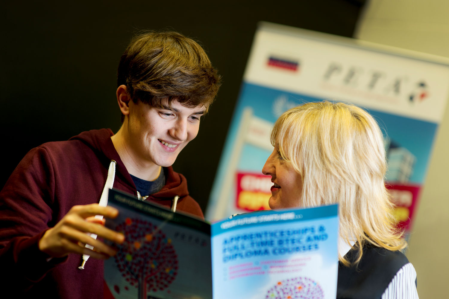 Young person looking at a brochure with an advisor