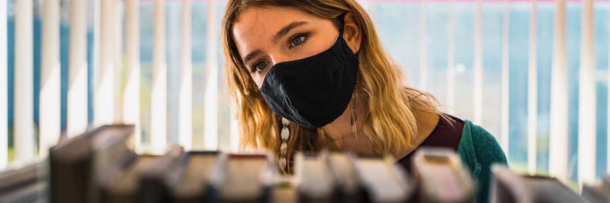 Girl in library wearing a mask