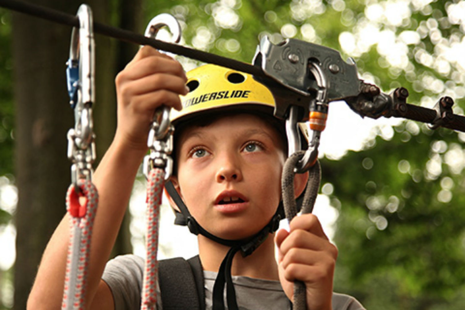 child in outdoor educational activity adjusting a harness