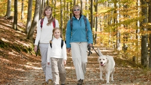 Family walking a dog in the woods