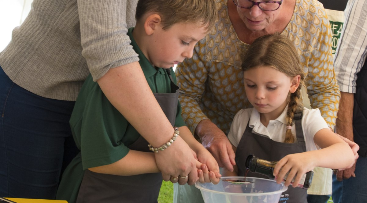 Two school children learning to cook